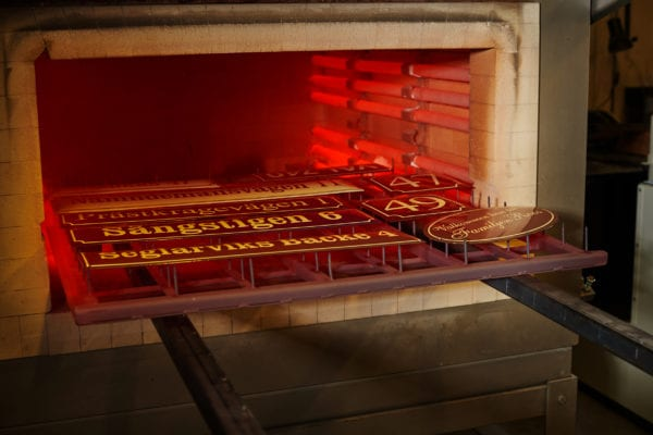 Skillinge Emalj emaljskylt - Den vita textemaljen har smält i 795 grader, detta är normalt skyltens tredje och sista bränning, varje färg bränns var för sig.