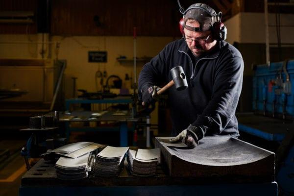 Skillinge Emalj emaljskylt - Robert kupar de valsade plåtarna med gummiklubba. Gjutjärnsformen kommer från gamla Kockums i Ronneby.